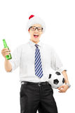 Smiling male with santa hat holding a beer bottle and ball Royalty Free Stock Photo