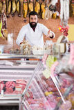 Smiling male seller grouping meat to sell. In butcher's shop Stock Photo