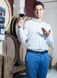 Smiling male seller holding glass of red wine in shop. With woods and tasting it Royalty Free Stock Photo