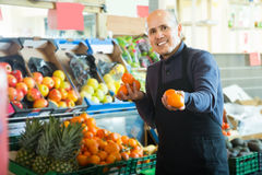 Smiling male seller offers mandarins Stock Images