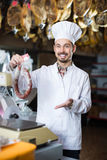 Smiling male seller weighing on scales sausage. In butcher's shop Stock Image