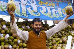 Smiling male selling coconuts hands up with fruits Stock Photos