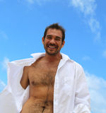 Smiling male with shirt open and blue sky Royalty Free Stock Images