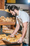 Smiling male shop assistant arranging fresh pastry. In supermarket Royalty Free Stock Photos