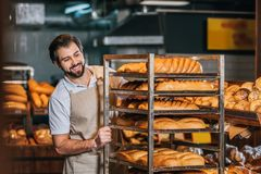 Smiling male shop assistant arranging fresh pastry. In supermarket Stock Images