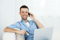 Smiling male shopping via internet Stock Photos
