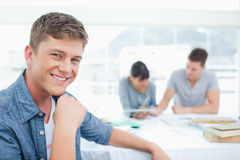 A smiling male sitting in front of his friends Stock Photography