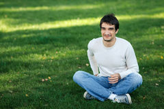 Smiling male sitting on the grass outdoors. Young smiling male sitting on the grass outdoors Stock Image