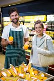 Smiling male staff assisting a woman with grocery shopping. Portrait of male staff assisting a women with grocery shopping in supermarket Stock Photography