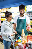 Smiling male staff assisting a woman with grocery shopping. Smiling male staff assisting a women with grocery shopping in supermarket Stock Photo