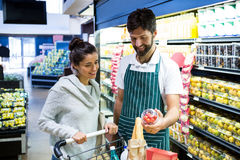 Smiling male staff assisting a woman with grocery shopping. Smiling male staff assisting a women with grocery shopping in supermarket Royalty Free Stock Images