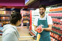 Smiling male staff assisting a woman with grocery shopping. Smiling male staff assisting a women with grocery shopping in supermarket Royalty Free Stock Photos