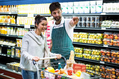 Smiling male staff assisting a woman in organic section. Smiling male staff assisting a women in organic section at supermarket Royalty Free Stock Photography