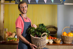 Smiling male staff holding leafy vegetables in basket at organic section. Of supermarket Royalty Free Stock Photo