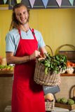 Smiling male staff holding leafy vegetables in basket at organic section. Of supermarket Stock Photo