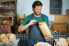 Smiling male staff packing bread in paper bag. In bakery shop Stock Photos