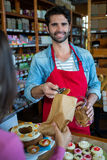 Smiling male staff putting cookies in paper bag Stock Photo