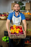 Smiling male staff standing with basket of bell peppers at organic section. In market Royalty Free Stock Image