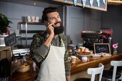 Smiling male staff talking on mobile phone at counter in coffee shop Stock Photos