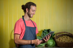 Smiling male staff using digital tablet in organic section. Of supermarket Royalty Free Stock Photos