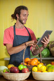 Smiling male staff using digital tablet in organic section. Of supermarket Royalty Free Stock Images