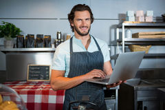 Smiling male staff using laptop at counter. Portrait of smiling male staff using laptop at counter in coffee shop Stock Image