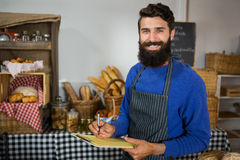 Smiling male staff writing on clipboard at counter in bakery shop Stock Photo