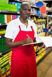 Smiling male staff writing on notepad in super market. Portrait of smiling male staff writing on notepad in super market Stock Photos