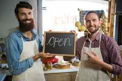Smiling male staffs holding a open sign Stock Photos