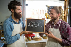 Smiling male staffs holding a open sign Stock Photography