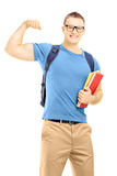 Smiling male student with backpack holding books and showing his. Biceps muscle isolated on white background Stock Photography