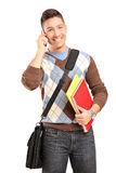 Smiling male student with bag and books talking on a phone. A smiling male student with shoulder bag and books talking on a cell phone isolated against white Royalty Free Stock Photo