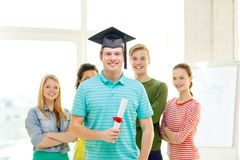Smiling male student with diploma and corner-cap. Education and people concept - smiling male student with diploma and corner-cap and friends on the back Stock Image
