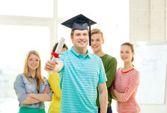 Smiling male student with diploma and corner-cap. Education and people concept - smiling male student with diploma and corner-cap and friends on the back Royalty Free Stock Photos