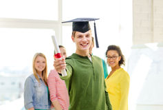 Smiling male student with diploma and corner-cap Stock Image