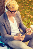 Smiling male student in eyeglasses with tablet pc. Education, technology and internet concept - smiling male student in eyeglasses with tablet pc and headphones Royalty Free Stock Images