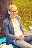 Smiling male student in eyeglasses with tablet pc. Education, technology and internet concept - smiling male student in eyeglasses with tablet pc and headphones Royalty Free Stock Photos