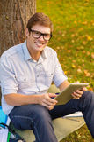 Smiling male student in eyeglasses with tablet pc Stock Photography