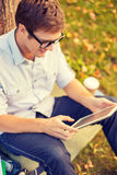 Smiling male student in eyeglasses with tablet pc Royalty Free Stock Image
