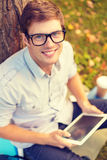 Smiling male student in eyeglasses with tablet pc Stock Image