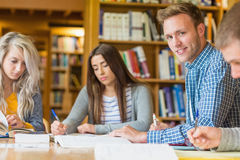 Smiling male student with friends at library desk Stock Images