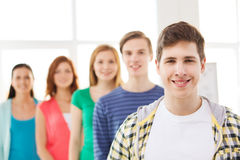 Smiling male student with group of classmates. Friendship and education concept - smiling male student in front of group of classmates Royalty Free Stock Images