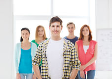 Smiling male student with group of classmates. Friendship and education concept - smiling male student in front of group of classmates Stock Photos