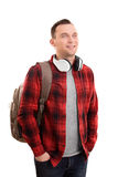 Smiling male student with headphones. A portrait of a smiling male student, wearing a backpack and headphones, isolated on white background Stock Image