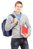 Smiling male student holding backpack and books. Isolated on white background Royalty Free Stock Images