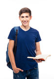 Smiling male student holding book. Smiling male student standing and holding book isolated on a white background. Looking at camera Royalty Free Stock Image