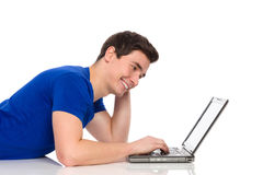 Smiling male student with laptop. Smiling young man working on laptop. Side view, waist up studio shot isolated on white Stock Images
