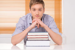 Smiling male student leaning on his hands. Royalty Free Stock Photo