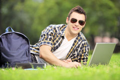 Smiling male student lying on a grass and working on a laptop. Smiling male student lying on a green grass and working on a laptop in park Royalty Free Stock Photography