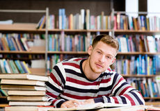 Smiling male student with open book working in a library.  Stock Images